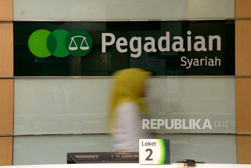 Petugas melayani nasabah ketika bertransaksi di kantor pelayanan Pegadaian Syariah, Jakarta, Jumat (4/1).