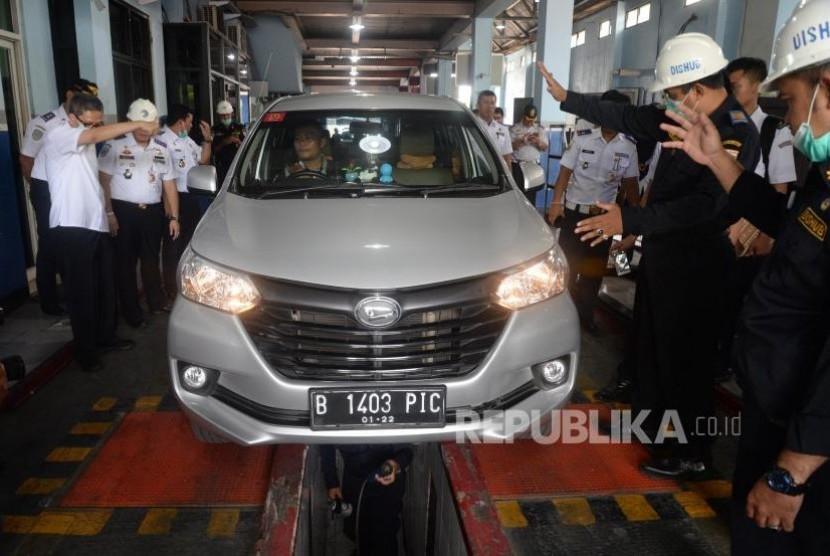 Petugas memeriksa mobil taksi daring saat uji kir di Unit Pengelola Pengujian Kendaraan Bermotor (UP-PKB) Pulogadung, Jakarta, Ahad (5/11).