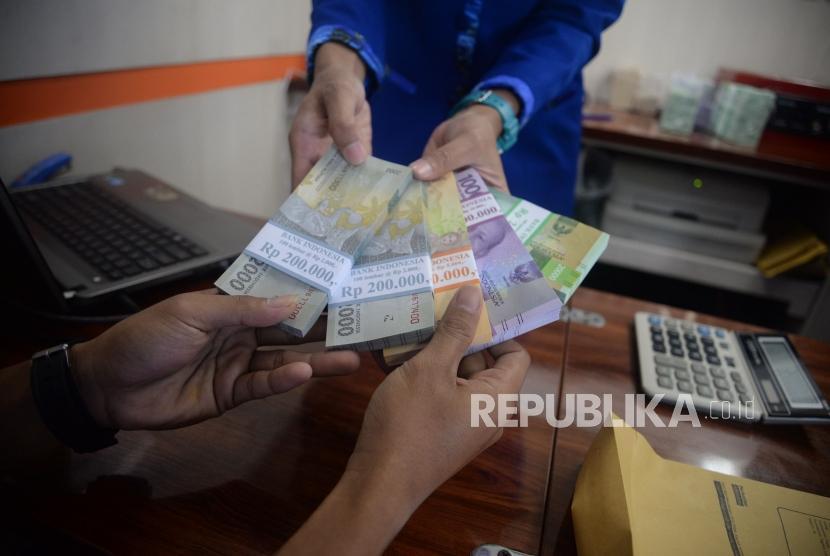 Petugas melayani penukaran uang pecahan kecil. (Ilustrasi)