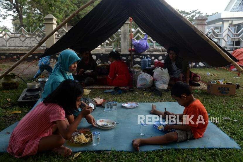 Sejumlah pengungsi korban bencana alam gempa bumi dan tsunami saat makan di Posko Pengungsian Rumah Dinas Gubernur, Palu, Sulawesi Selatan, Rabu (3/10).