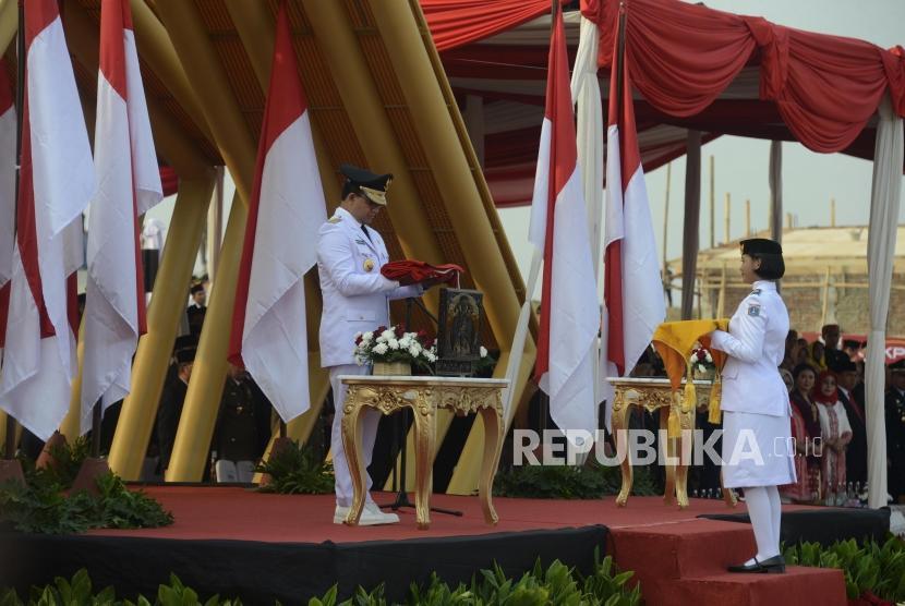 Gubernur DKI Jakarta Anies Baswedan selaku inspektur upacara saat akan memberikan bendera untuk dikibarkan pada peringatan hari kemerdekaan RI di Pantai Maju, Jakarta, Sabtu (17/8).