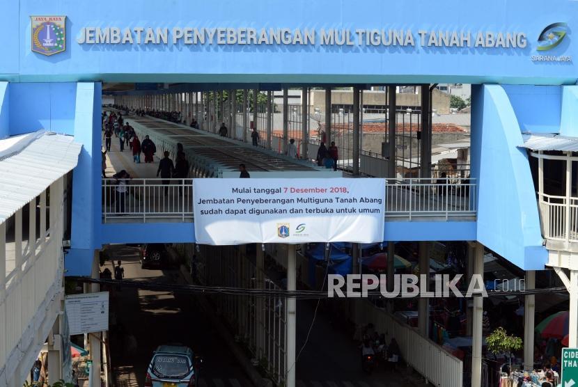 Pejalan kaki melintasi skybridge atau Jembatan Penyeberangan Multiguna (JPM) Tanah Abang, Jakarta, Jumat (7/12).