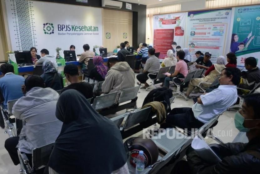 Petugas melayani warga di kantor Badan Penyelanggara Jaminan Sosial (BPJS) Kesehatan KCU Jakarta Pusat, Rabu (1/11).