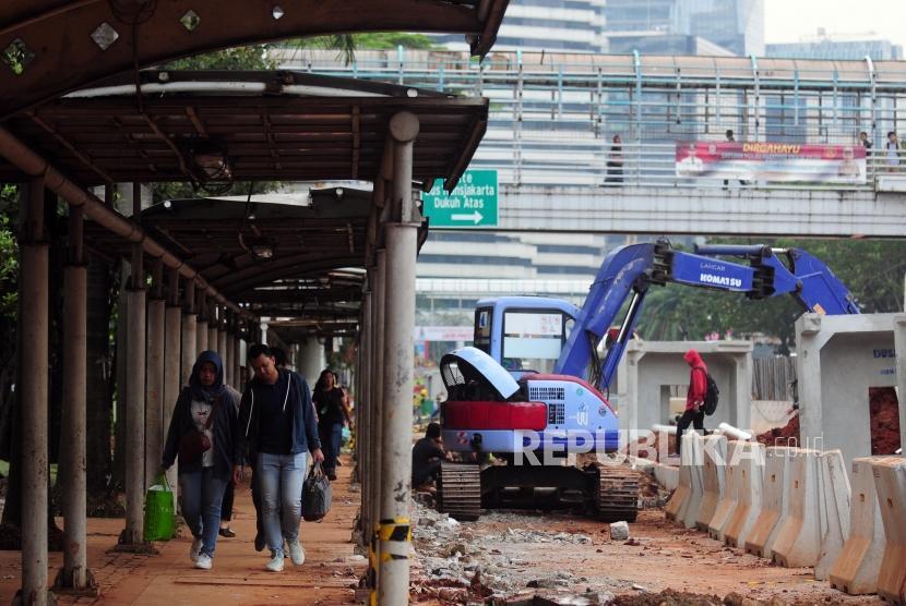 Warga berjalan kaki di dekat proyek penataan trotoar di kawasan Sudirman, Jakarta Pusat, Jumat (29/6).