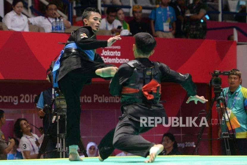 Pesilat Indonesia Abdul Malik (pita biru) bertanding melawan pesilat Malaysia Muhammad Faizul M Nasir pada babak final cabang pencak silat putra kelas B 50-55 kg Asian Games 2018 di Padepokan Pencak Silat, TMII, Jakarta, Senin (27/8).