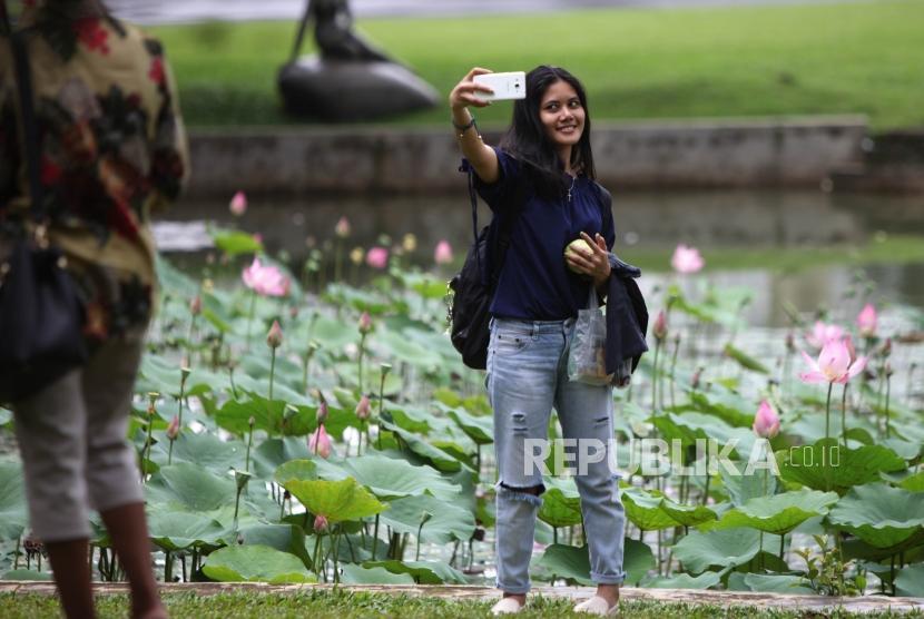 Warga berfoto selfie saat berwisata di Kebun Raya Bogor, Jawa Barat, Sabtu (23/12).
