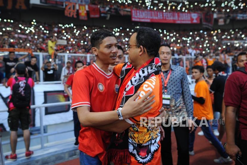 Gubernur DKI Jakarta Anies Baswedan memeluk seorang suporter Persija Jakarta seusai laga melawan Mitra Kukar di Liga 1 2018 di Stadion Utama Gelora Bung Karno, Jakarta, Ahad (9/12).
