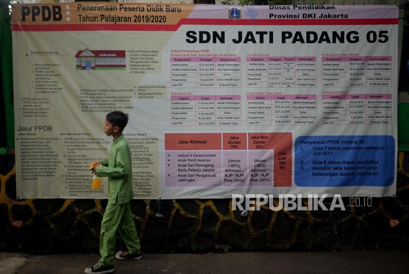 Seorang anak melintas didekat pengumuman penerimaan peserta didik baru (PPDB) online tahun pelajaran 2019/2020 yang dipajang di SDN Jati Padang 05, Jakarta, Jumat (14/6).