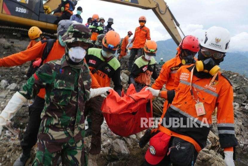 Relawan ACT bersama TNI dan tim evakuasi bencana lainnya mengangkat jenazah yang baru ditemukan di perumnas Balaroa, Palu, Sulawesi Tengah, Kamis (11/10).