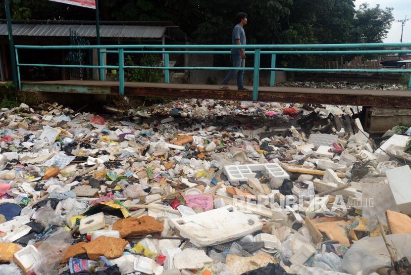 Warga berjalan di atas jembatan sungai yang aliran airnya dipenuhi tumpukan sampah di anak Sungai Ciliwung Kali Baru, Bojong Gede, Bogor, Jawa Barat, Kamis (31/1).