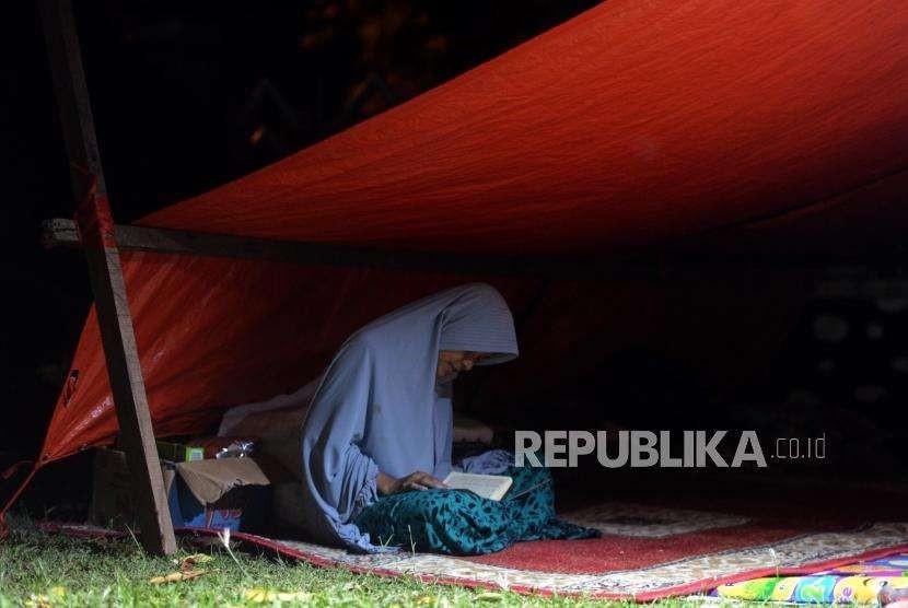 Sejumlah pengungsi korban bencana alam gempa bumi dan tsunami saat membaca Al Quran di Posko Pengungsian Rumah Dinas Gubernur, Palu, Sulawesi Selatan, Rabu (3/10).