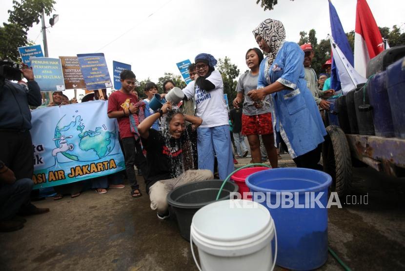 Puluhan warga yang tergabung dalam Koalisi Masyarakat Menolak Swastanisasi Air Jakarta (KMMSAJ) melakukan mandi bersama saat aksi unjuk rasa di Depan Gedung Balai Kota Jakarta, Kamis (22/3).