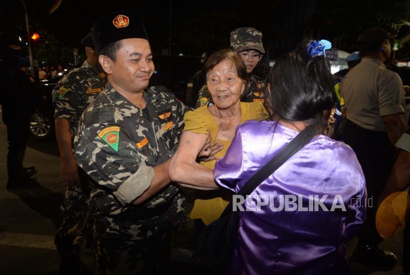 Anggota Banser membantu tim gabungan TNI dan Polri dalam pengamanan natal di Gereja Katderal, Jakarta, (24/12) malam.