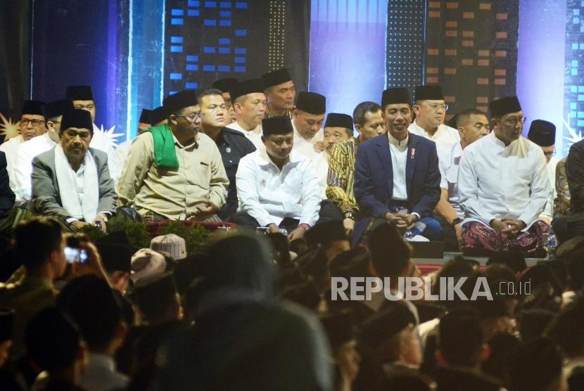 Presiden RI Joko Widodo (Jokowi) duduk bersama para ulama dan pejabat di hadapan ribuan santri pada malam puncak peringatan Hari Santri Nusantara, di Lapangan Gasibu, Kota Bandung, Ahad (21/10).