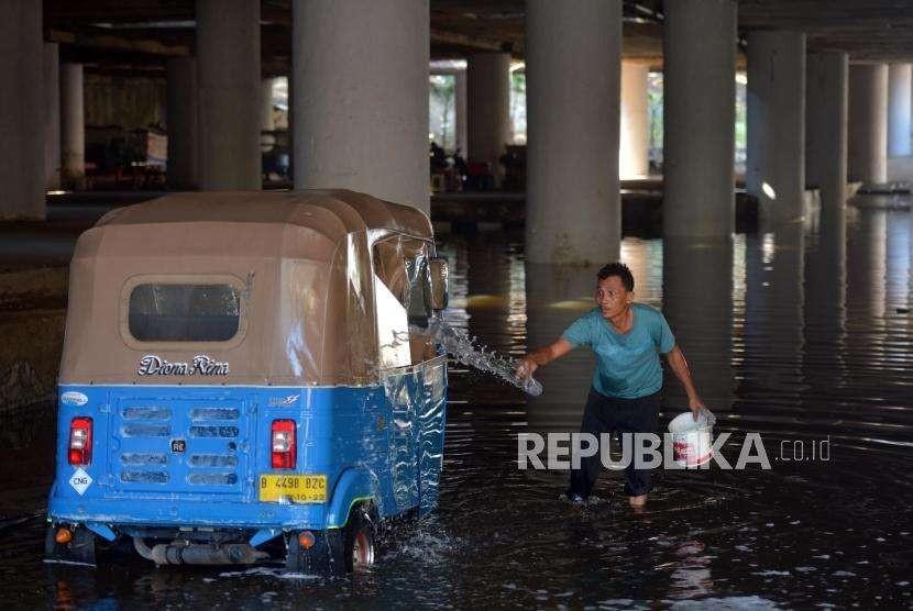 Supir bajaj mencuci kendaraannya memanfaatkan genangan air di Terowongan Apron, Jalan HBR Motik, Kemayoran, Jakarta, Selasa (11/9).