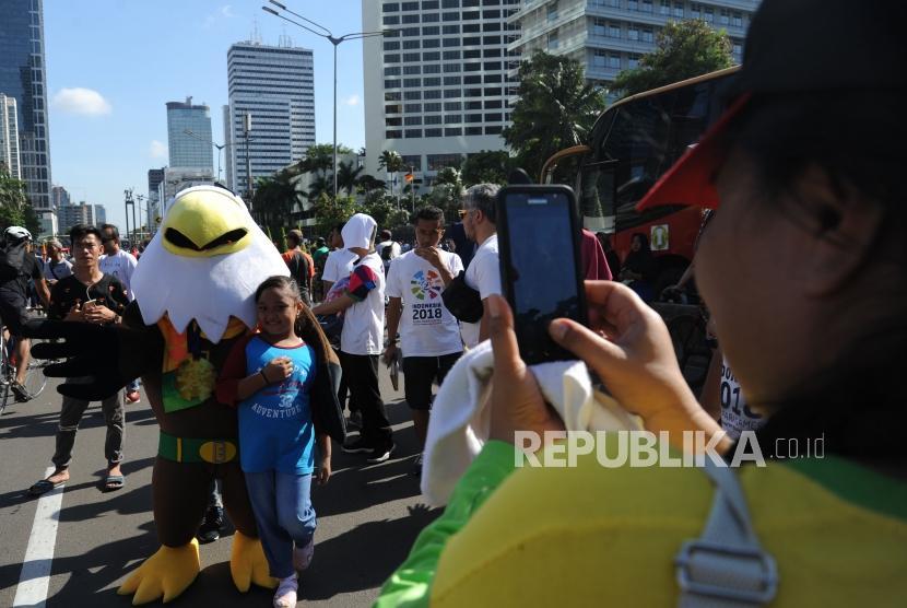 Seorang anak berfoto dengan maskot Asian Paragames Momo   dikawasan hari bebas berkendara / Car Free Day di Bundaran HI, Jakarta (1/4).