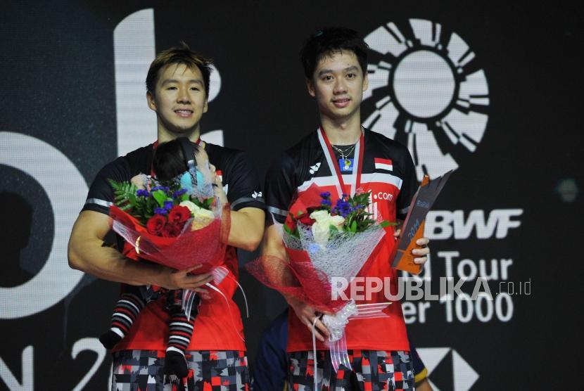 Ganda putra Indonesia Marcus Fernaldi Gideon (kiri) dan Kevin Sanjaya Sukamuljo berada di atas podium setelah bertanding mengalahkan ganda putra Indonesia Mohammad Ahsan dan Hendra Setiawan pada final Blibli Indonesia Open 2019 di Istora Gelora Bung Karno, Jakarta, Ahad (21/7).