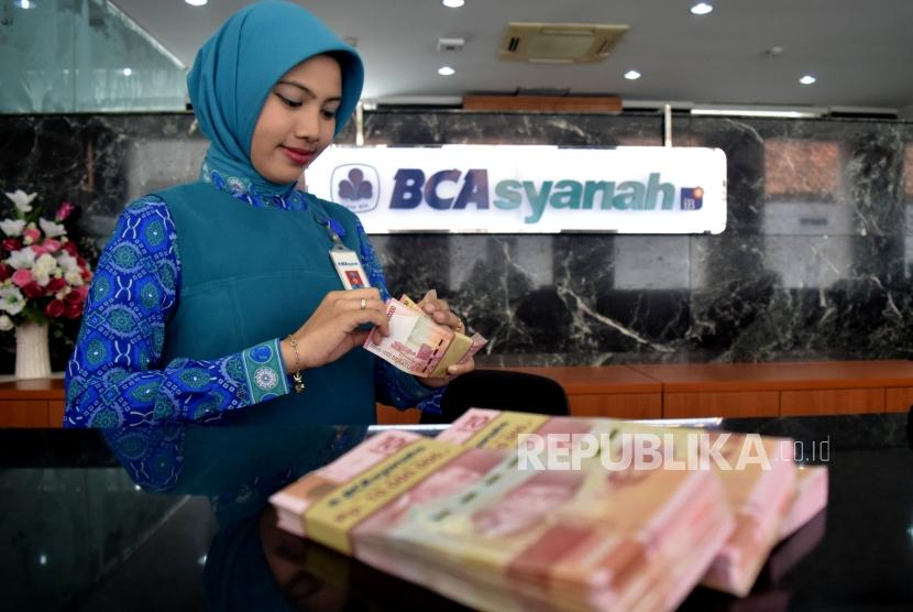 Petugas menghitung uang nasabah ketika transaksi di kantor layanan BCA Syariah, Jakarta, Selasa (6/11).