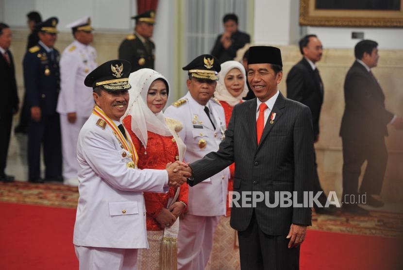 Presiden Joko Widodo memberikan ucapan selamat kepada Gubernur Riau terpilih Syamsuar dan Wakil Gubernur Riau terpilih Edi Natar Nasution seusai acara pelantikan di Istana Negara, Jakarta (20/2/2019).