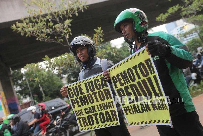 Pengemudi ojek online melakukan aksi bela trotoar (ABT) yang bertajuk 'gue pemotor, gue enggak lewat trotoar' di Kawasan Kota Kasabelangka, Jakarta, Kamis (23/8).
