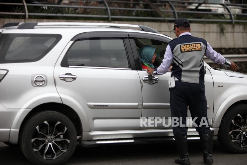 Petugas Dishub mengarahkan kepada pengendaran mobil bernomor polisi ganjil saat hari pertama pemberlakuan sistem ganjil genap di Gerbang Tol Bekasi Barat 1, Bekasi, Jawa Barat, Senin (12/3).