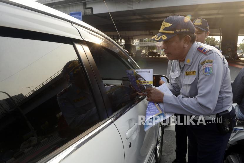 Petugas Dinas Perhubungan DKI Jakarta saat melakukan sosialisasi uji coba perluasan sistem ganjil genap kepada pengendara di kawasan Pramuka, Jakarta, Senin (12/8).
