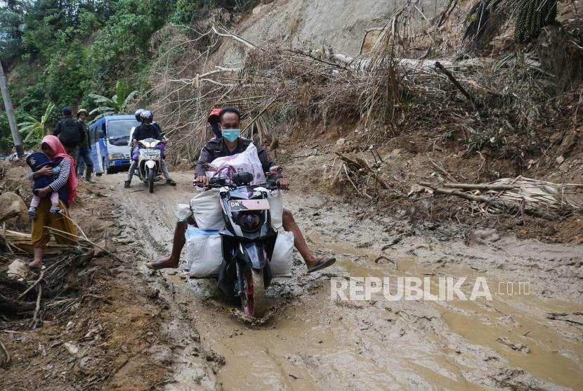 Sebuah sepeda motor melintas di ruas jalan Trans Kulawi Kecamatan Kulawi, Kabupaten Sigi, Sulawesi Tengah yang sempat terputus karena longsor, Rabu (10/10).