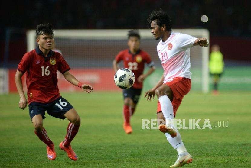 Pesepak bola Indonesia  Ilham Udin Afmaiyn berusaha melewati pemain Laos pada laga penyisihan Grup A cabang sepak bola Asian Games 2018 di Stadion Patriot, Bekasi, Jumat(17/8).