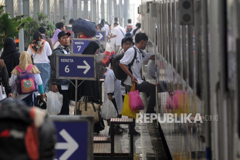 Warga bersiap menaiki kereta saat mudik gratis BUMN 2018 di Stasiun Pasar Senen, Jakarta, Kamis (7/6).