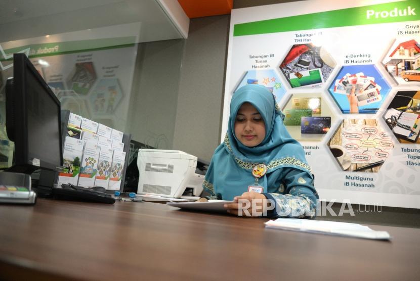 Target Buku III. Petugas melayani transaksi nasabah di kantor layanan BNI Syariah, Jakarta, Selasa (3/7).