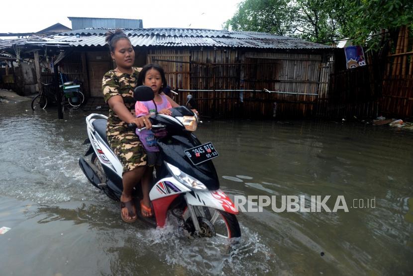 Warga melintasi genangan air saat terjadi banjir rob di kawasan Muara Angke, Jakarta Utara, Selasa (22/1).