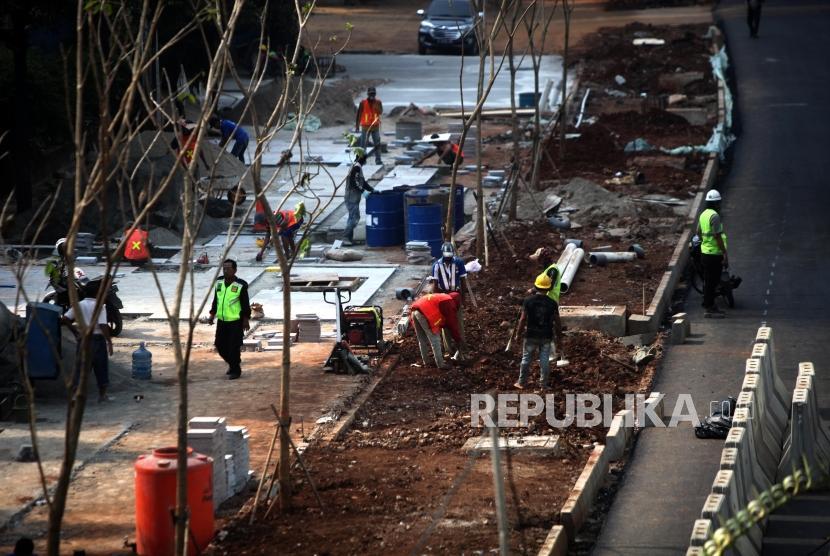 Sejumlah pekerja menyelesaikan proyek pembangunan pedestrian di Jalan Sudirman, Jakarta, Ahad (1/7).