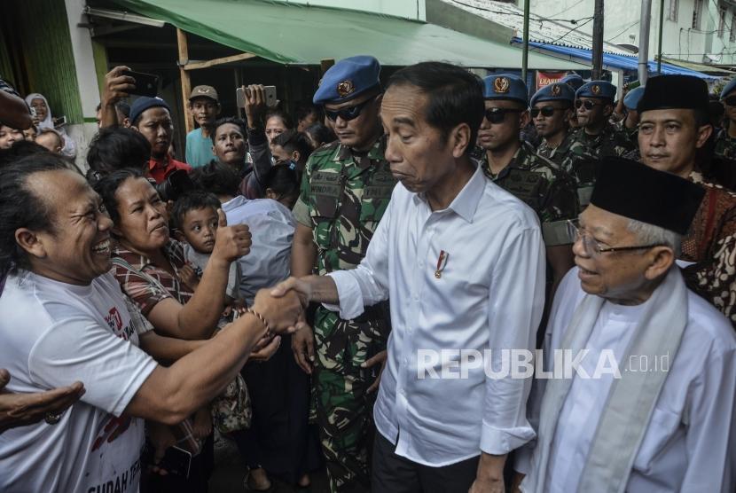 Capres Petahana Joko Widodo (tengah) bersama Cawapres Ma'ruf Amin (kanan) menyapa warga usai pidato kemenangan sebagai Presiden periode 2019-2024 di Kampung deret,Tanah tinggi,Johor baru, Jakarta Pusat, Selasa (21/5).