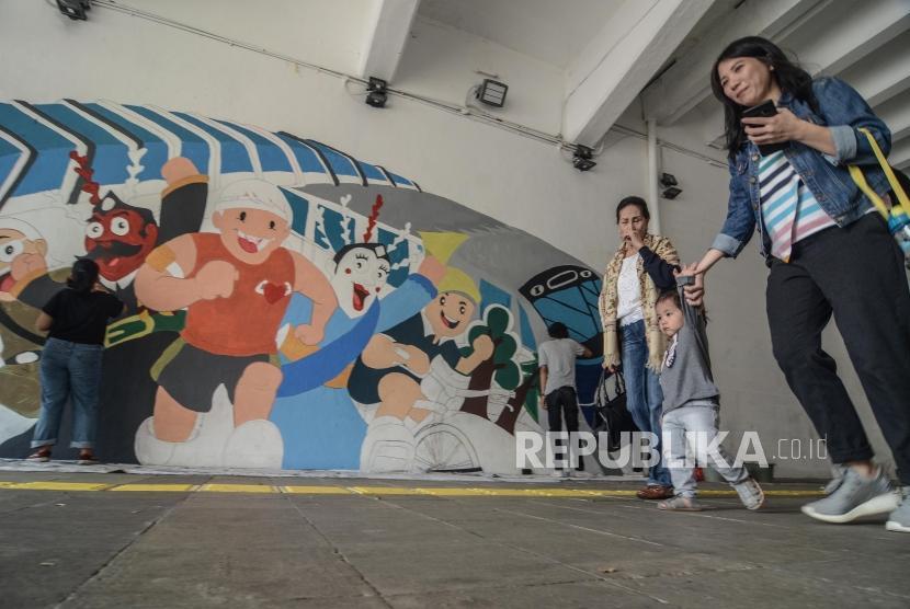 """Mural Wajah baru Jakarta.Sejumlah mahasiswa melintasi mural bertemakan """"Wajah Baru Jakarta"""" di Terowongan Kendal, Jakarta Pusat, Kamis (20/6)."""