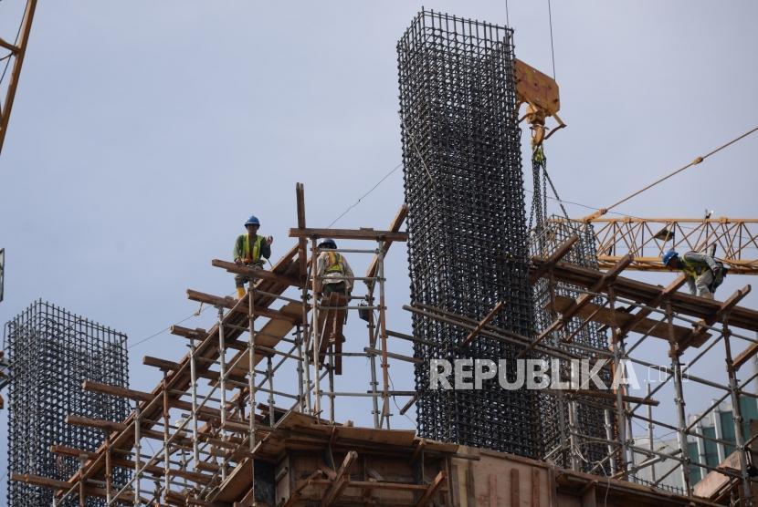 Pekerja beraktivitas dipembangunan gedung bertingakat di Jakarta, Ahad (30/12).