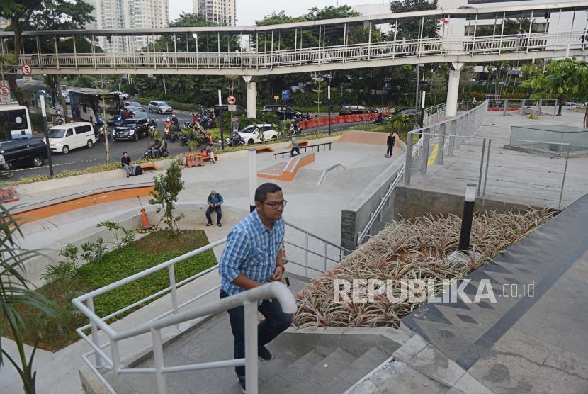 Warga melintas di Taman Spot Budaya, Dukuh Atas, Jakarta, Selasa (16/7).