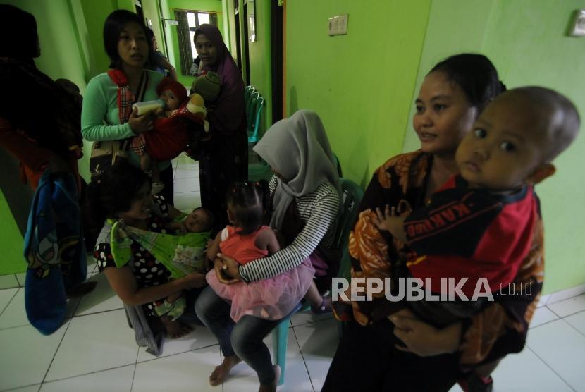 Sejumlah warga mengantre sebelum melakukan imunisasi difteri untuk anaknya di Puskemas Cimanggis, Depok, Jawa Barat, Rabu (6/12).