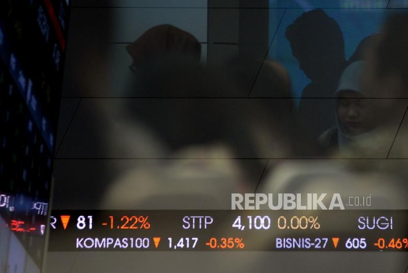 Pengunjung berada di dekat layar elektronik Indeks Harga Saham Gabungan (IHSG) di Gedung Bursa Efek Indonesia (BEI) Jakarta.