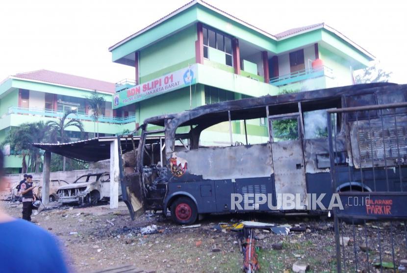 Bangkai mobil yang terbakar di area Kompleks Asrama Brimob Petamburan, Jakarta, Rabu (22/5).