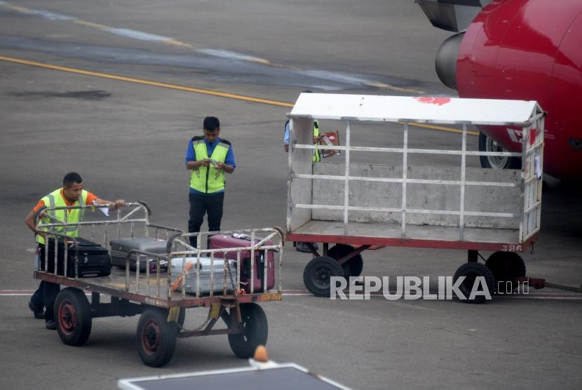 Petugas masukan barang milik penumpang ke bagasi pesawat di Bandara Internasional Soekarno-Hatta, Tanggerang,Banten, Kamis (7/2).