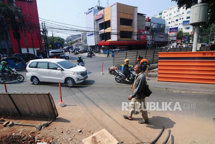 Renovasi Trotoar Cikini. Pejalan kaki melintasi pengerjaan revitalisasi trotoar di Jalan Cikini, Jakarta Pusat, Senin (1/7).