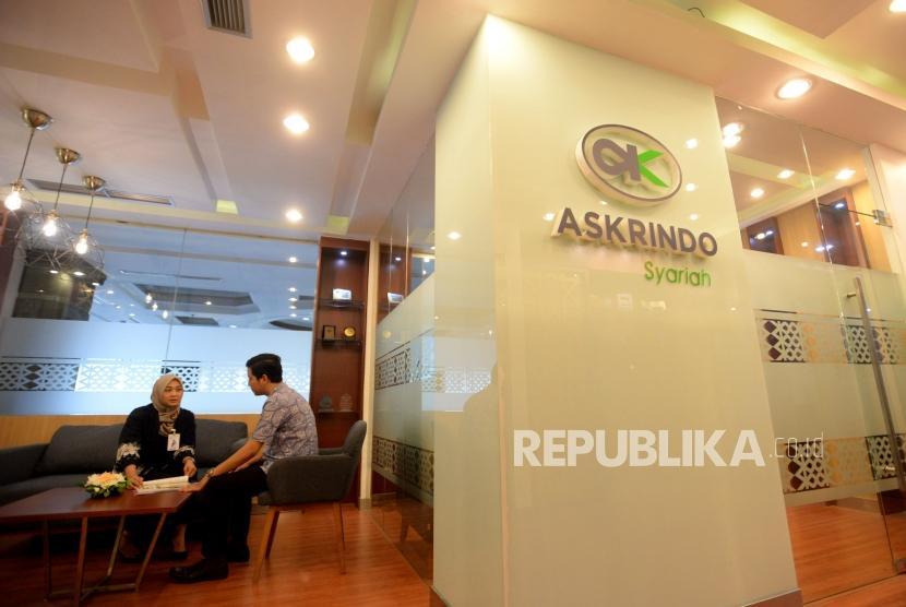 Karyawan melayani nasabah di Kantor Askrindo Syariah, Jakarta.