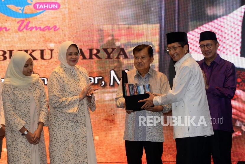 Imam Besar Masjid Istiqlal Nasaruddin Umar memberikan buku karanganya kepada Wakil Presiden Jusuf Kalla pada acara tasyakuran 60 tahun dan peluncuran buku di Jakarta, Ahad (23/6).