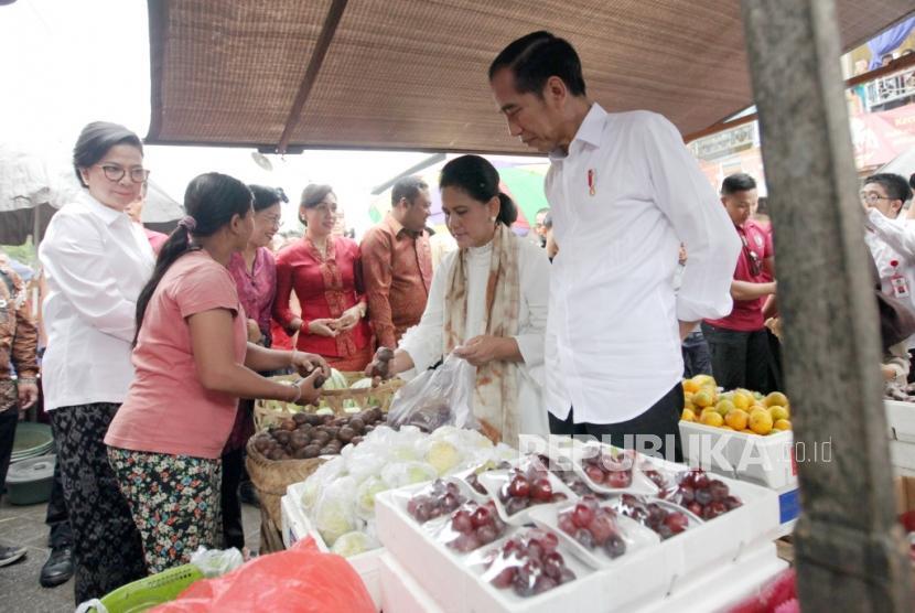 Presiden Joko Widodo beserta ibu negara Iriana Joko Widodo berbelanja buah di Pasar Sukawati, Gianyar, Bali, Jumat (14/6).