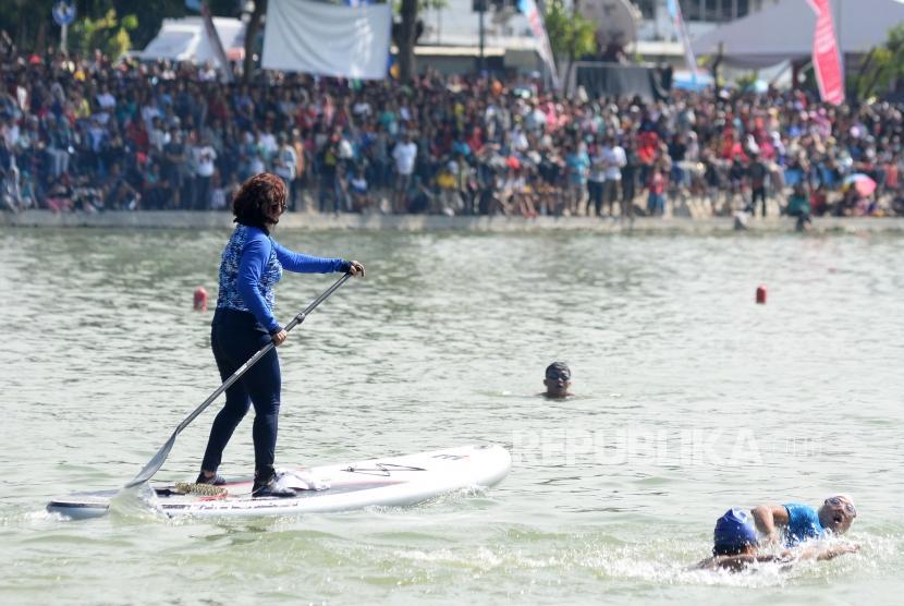 Menteri Kelautan dan Perikanan Susi Pudjiastuti dengan menaiki Paddle Board dan Wagub DKI Jakarta Sandiaga Uno berenang saat kompetisi adu cepat dalam festival Danau Sunter, Jakarta, Ahad (25/2).