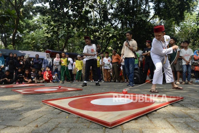 Anak-anak bermain gangsing pada acara Festival Permainan Tradisional Anak Betawi di Hutan Kota Srengseng, Jakarta, Sabtu (3/8).
