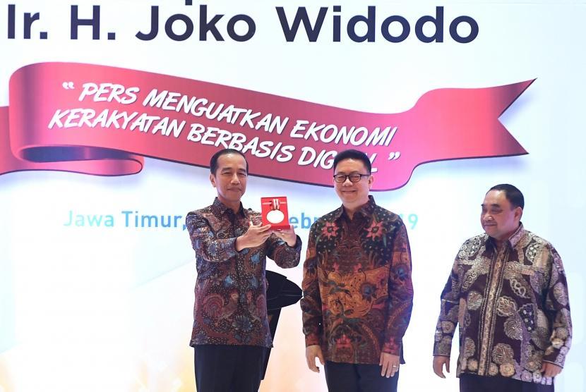Presiden Joko Widodo (kiri) didampingi Ketua Dewan Pers Yosep Adi Prasetyo (tengah) dan Penanggung jawab HPN 2019 Margiono (kanan) menunjukan medali kemerdekaan pers saat puncak perayaan Hari Pers Nasional (HPN) di Surabaya, Jawa Timur, Sabtu (9/2/2019).
