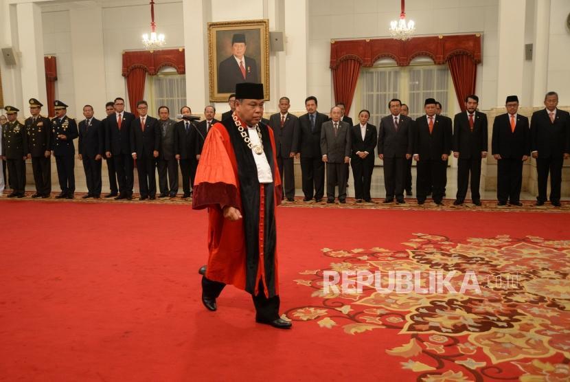 Pelantikan Hakim MK. Hakim Konstitusi Arief Hidayat menuju meja penandatanganan berita acara usai membaca sumpah jabatan di depan Presiden Joko Widodo saat pelantikan Hakim Konstitusi di Istana Negara, Jakarta, Selasa (27/3).