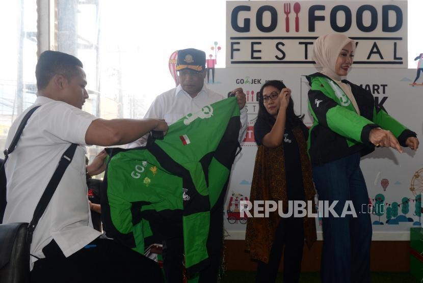 Menteri Perhubungan Budi Karya Sumadi saat akan memakai jaket ojek online di Transmart Carrefour, Depok, Jawa Barat, Sabtu (5/1).