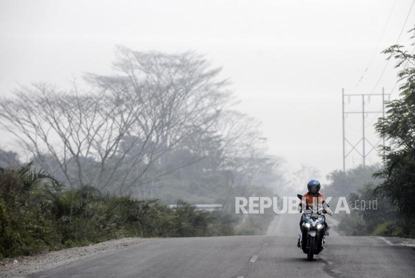 Pengendara motor melintas saat kabut asap kebakaran hutan dan lahan menyelimuti Pekanbaru, Riau, Selasa (10/9).